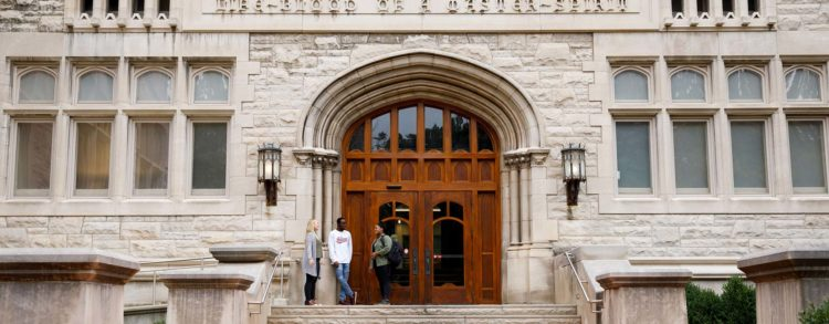 Three people stand in the doorway of Franklin Hall