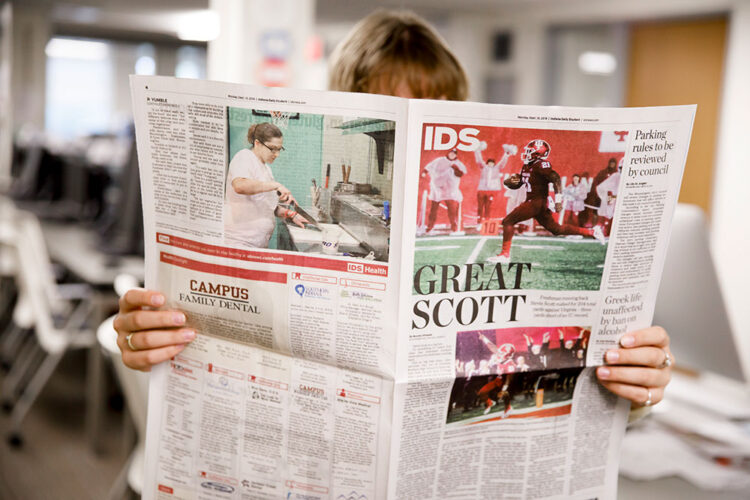 A woman reading the Indiana Daily Student newspaper