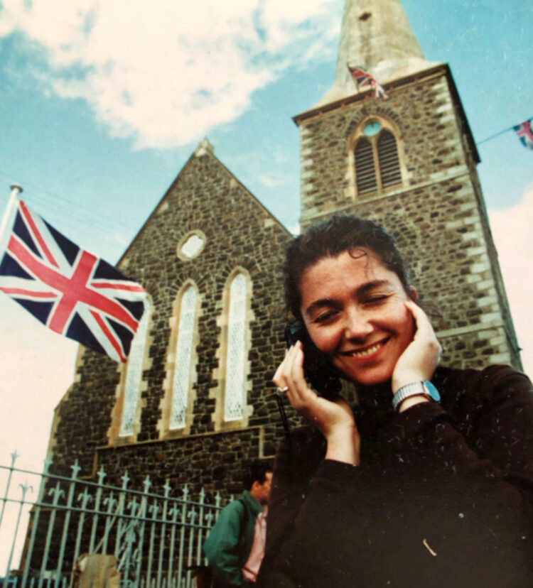 Elaine Monaghan talks on a cell phone outside a building that's flying a British flag