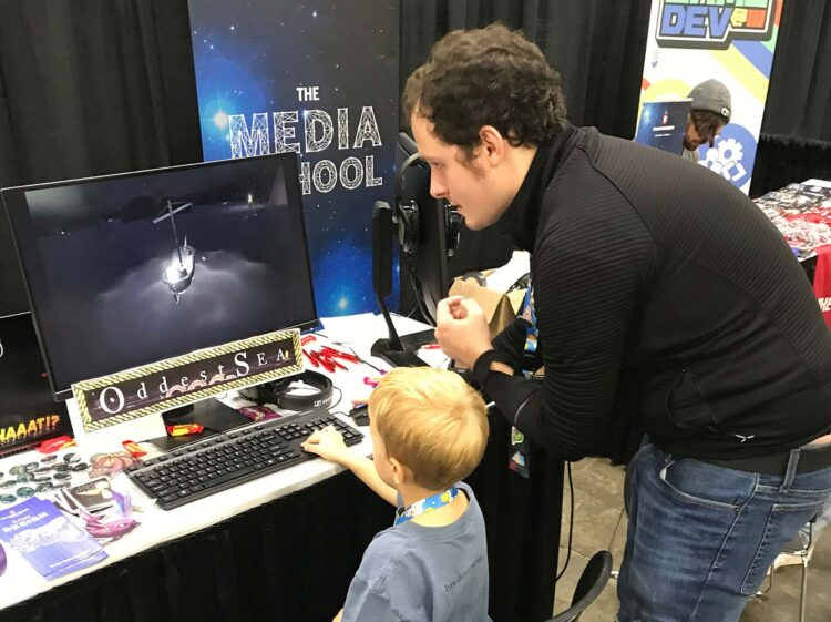 Matt Olry shows a child how to play his video game,